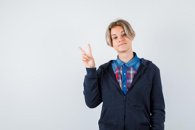 Ładny nastoletni chłopak w koszuli, bluzie z kapturem, pokazując znak v i patrząc wesoło, widok z przodu.