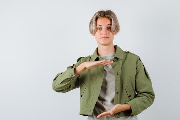 Ładny nastoletni chłopak w zielonej kurtce pokazujący duży znak i patrzący z nadzieją