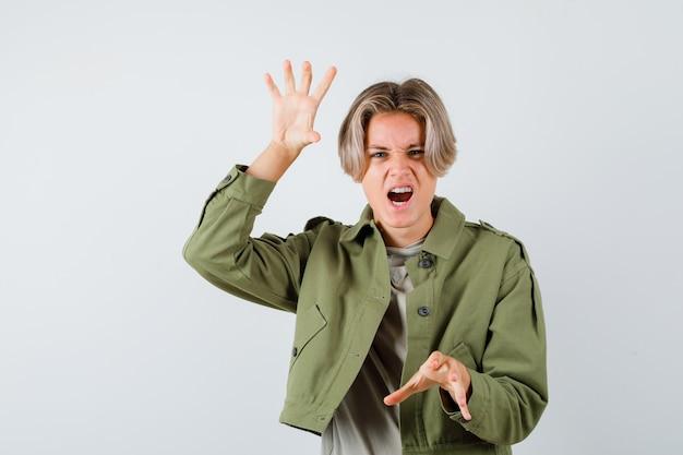Ładny nastoletni chłopak w zielonej kurtce pokazujący pazury imitujące kota, podczas gdy krzyczy i wygląda agresywnie