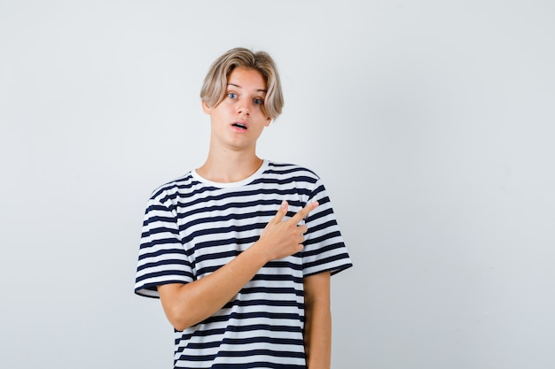 Ładny nastoletni chłopak wskazujący na prawy górny róg w pasiastym t-shircie i wyglądający na zdziwionego. przedni widok.