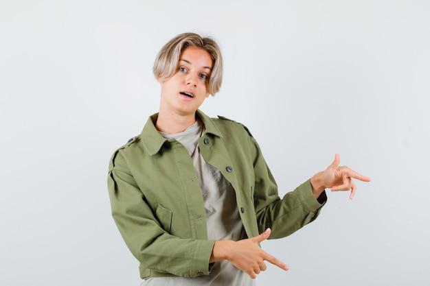 Ładny nastoletni chłopak wskazujący w prawo w zielonej kurtce i patrzący z wahaniem
