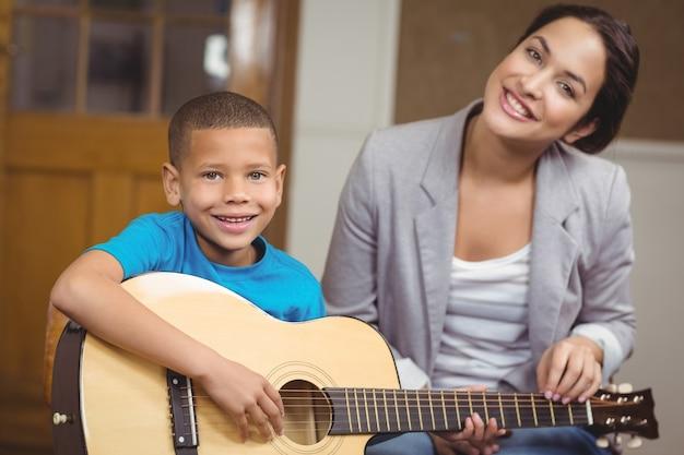 Ładny nauczyciel daje lekcje gry na gitarze dla ucznia