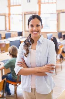 Ładny nauczyciel ono uśmiecha się przy kamerą przy plecy sala lekcyjna