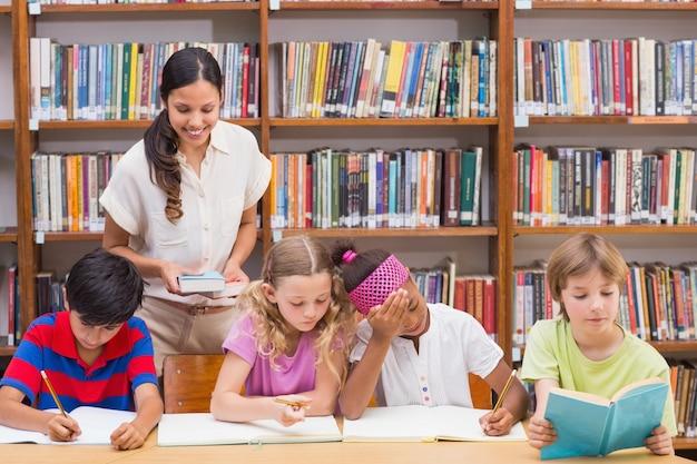 Ładny nauczyciel pomaga uczniom w bibliotece