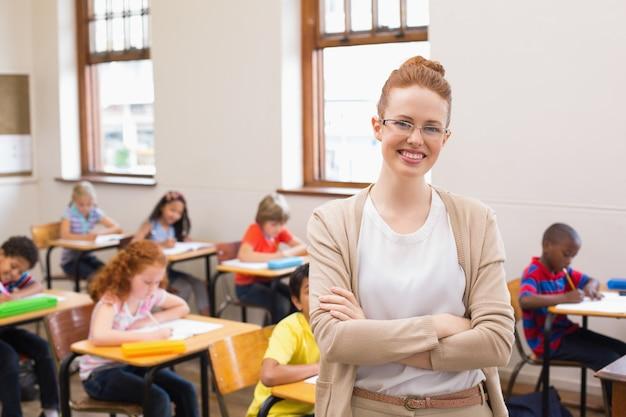 Ładny nauczyciel uśmiecha się do kamery w klasie w klasie