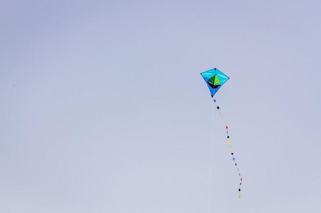Ładny niebieski latawiec latający na błękitne niebo