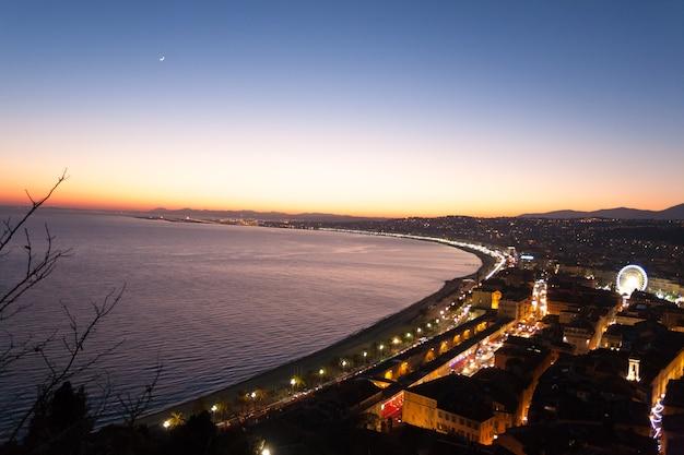 Ładny nocny krajobraz plaży, francja. ładna plaża i słynny chodnik angielski, promenade des anglais. słynne francuskie miasto turystyczne