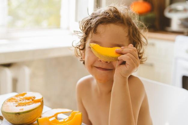 Ładny piękny mały chłopiec jedzenie świeżego melona.