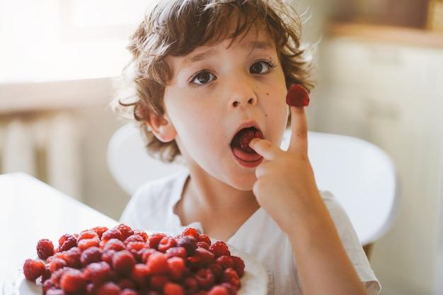 Ładny piękny mały chłopiec jedzenie świeżych malin. zdrowa żywność, dzieciństwo i rozwój.