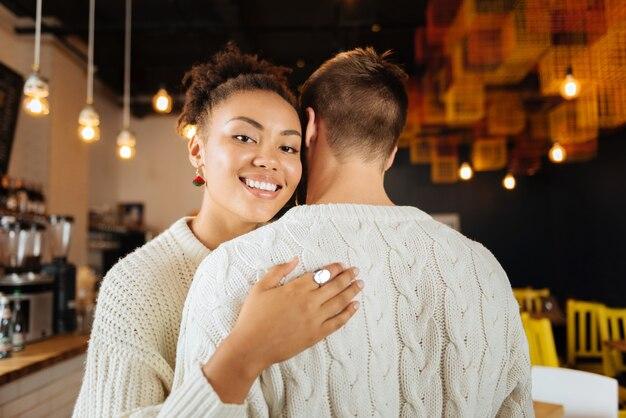 Ładny pierścionek. uśmiechnięta kobieta rozpromieniona nosząca ładny pierścionek i kolczyki przytulanie jej przystojnego męża
