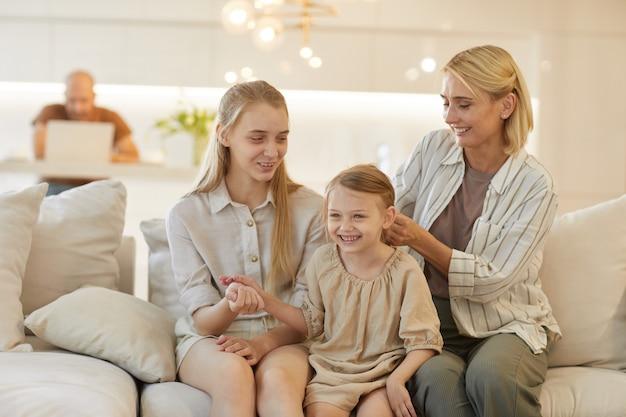 Ładny portret beztroskiej matki splatającej włosy córeczki siedząc na kanapie i ciesząc się razem w domu
