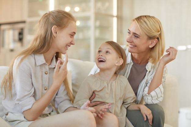 Ładny portret beztroskiej młodej matki rozmawiającej z dwiema córkami i uśmiechającej się wesoło, ciesząc się razem w domu