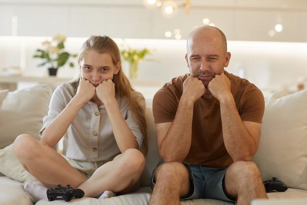 Ładny portret dojrzałego ojca i nastolatki, pozujących razem podczas grania w gry wideo, siedząc na kanapie w przytulnym wnętrzu domu