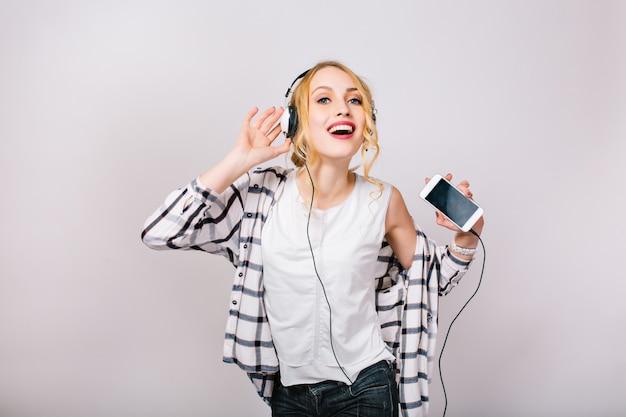 Ładny portret zachwycony wspaniałej kobiety o blond włosach. muzyka szczęśliwa dziewczyna tańczy przeciwko czasowi imprezy. wolny czas. aktywny, pozytywny styl życia