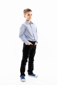 Ładny poważny chłopak uczeń stoi trzymając ręce w kieszeniach
