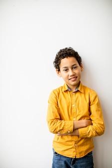 Ładny pozytywny mały chłopiec kręcone włosy stojący przy białej ścianie