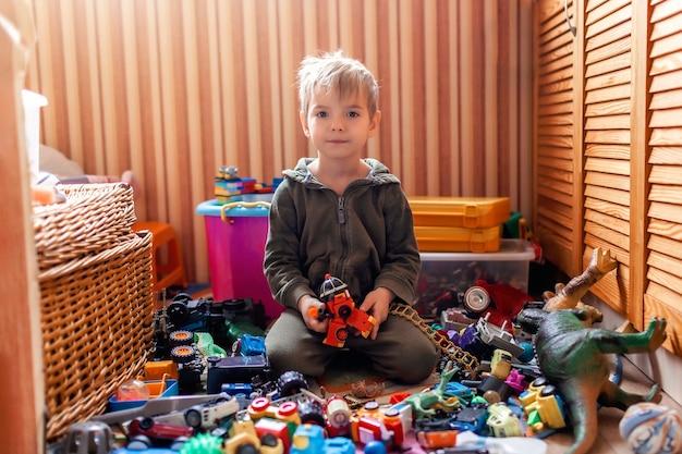 Ładny przedszkolak chłopiec siedzi na podłodze wśród wielu zabawek, aktywność domowa podczas blokady