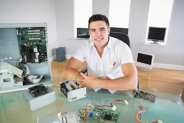 Ładny przyglądający inżyniera komputerowego obsiadanie przy biurkiem ono uśmiecha się przy kamerą
