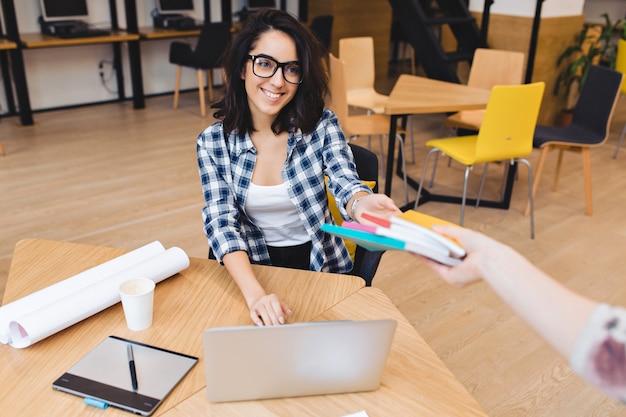Ładny przyjazny brunetka młoda kobieta w czarnych okularach przy stole, biorąc książki i uśmiechając się do klienta. studia na uczelni, praca jako freelancer, wielki sukces, świetny zespół.