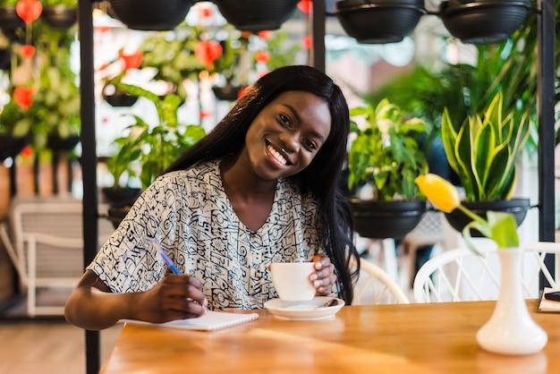 Ładny, przyjemny african american kobieta robienia notatek w zeszycie