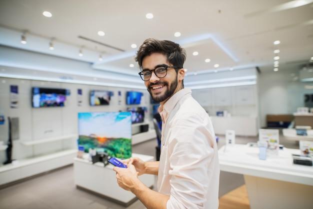 Ładny przystojny młody człowiek stojący w jasnym sklepie elektronicznym i patrząc w kamerę. testowanie nowych telefonów.