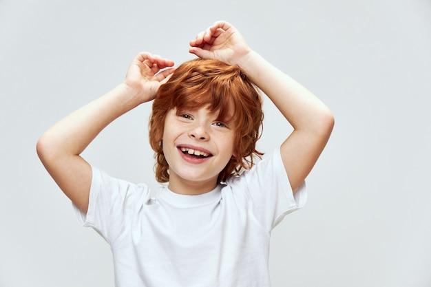 Ładny rudowłosy chłopak trzymając się za ręce na głowie uśmiech biała koszulka szare tło dzieciństwo