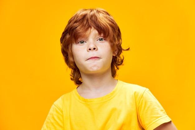 Ładny rudowłosy chłopiec zbliżenie przycięte widok żółte tło
