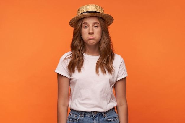 Ładny rudowłosy młoda kobieta pozuje z zdenerwowaną twarzą, patrząc i grymasując, pozowanie