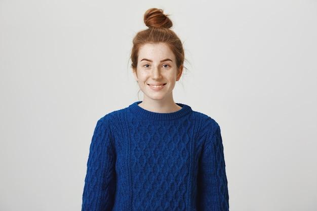 Ładny rudy hipster dziewczyna z fryzurą kok, uśmiechając się