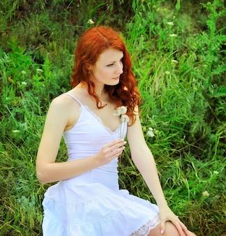 Ładny rudy kobieta w białej sukni siedzi na trawie w parku z mniszek lekarski w jej ręce.