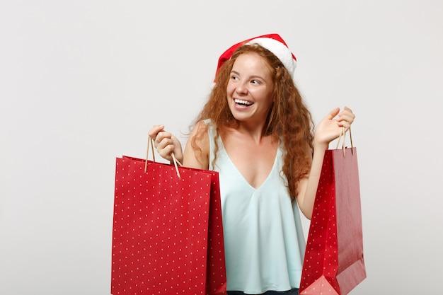 Ładny rudy santa dziewczyna w boże narodzenie kapelusz na białym tle. szczęśliwego nowego roku 2020 celebracja wakacje koncepcja. makieta miejsca na kopię. po zakupach trzymaj torbę z prezentami lub zakupami.