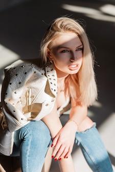 Ładny seksowny model kobiety w stylowej beżowej skórzanej kurtce w dżinsach vintage z blond włosami o niebieskich oczach z pulchnymi seksownymi ustami pozuje na zewnątrz w jasny wiosenny słoneczny dzień