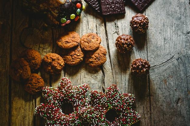 Ładny skład z ciepłym światłem świąteczne słodycze i ciasteczka czekoladowe, tło uroczysty ułożone na prosty drewniany stół