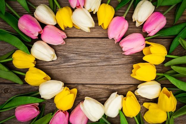Ładny skład z kolorowych tulipanów z miejsca kopiowania na drewniane