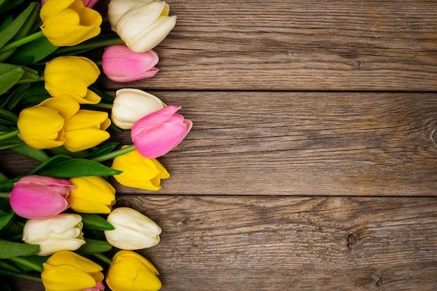 Ładny skład z tulipanami z kopii przestrzenią na drewnianym