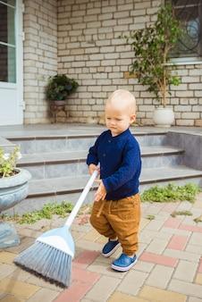 Ładny śliczny kaukaski chłopiec maluch grający na miotle na podwórku w ogrodzie na zewnątrz