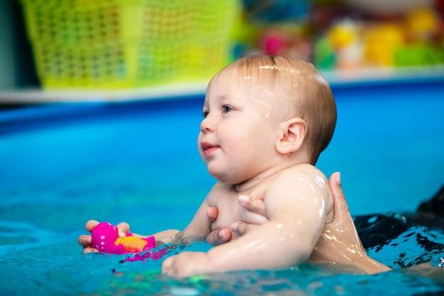 Ładny smutny chłopiec uczy się pływać w specjalnym basenie dla małych dzieci. zajęcia dla dzieci. ćwiczenia z trenerem