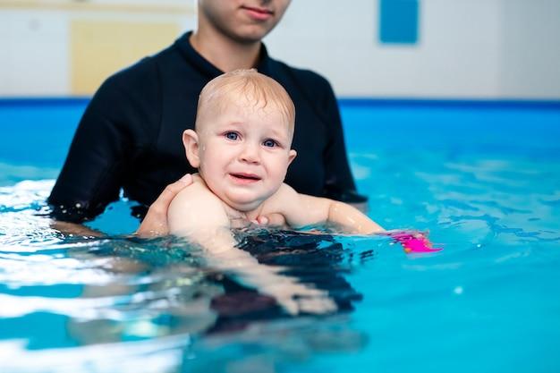 Ładny smutny chłopiec uczy się pływać w specjalnym basenie dla małych dzieci