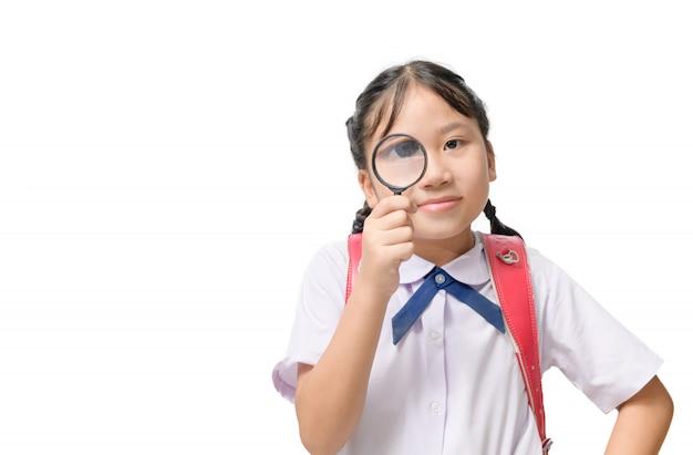 Ładny student dziewczyna w okularach i trzymając szkło powiększające na białym tle
