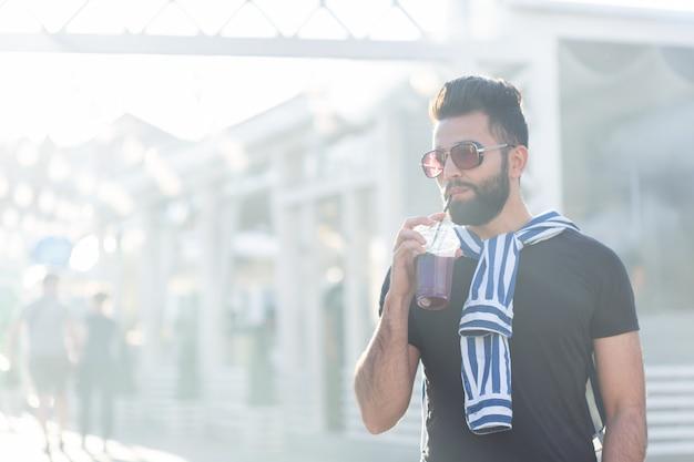 Ładny stylowy arabski młody mężczyzna hipster z wąsami i brodą i noszenie okularów do picia soku ze słomką. koncepcja wakacji letnich.