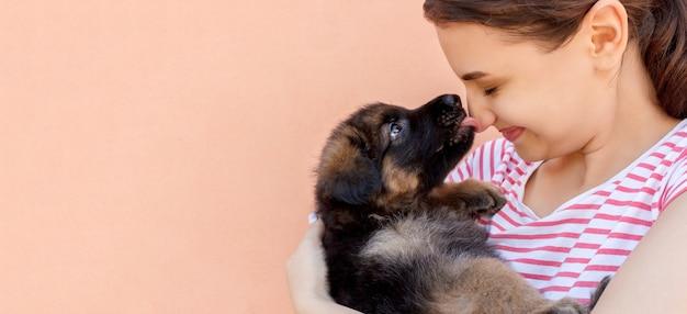 Ładny szczeniak owczarek niemiecki całuje nos kobiety