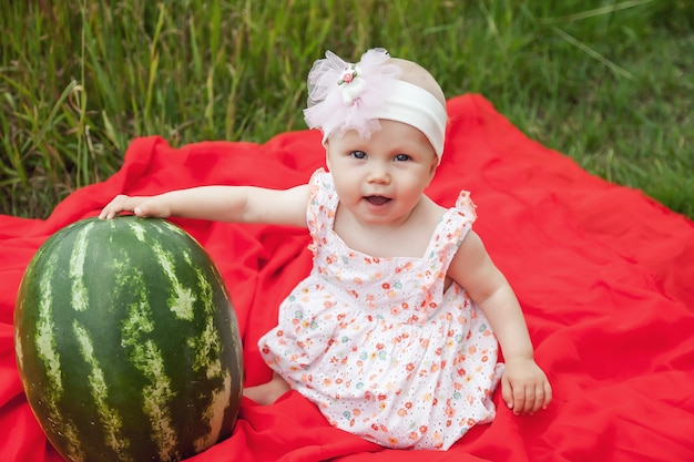 Ładny szczęśliwy blondynka o niebieskich oczach dziewczyna 8 miesięcy w trawie z arbuza. pojęcie zdrowego odżywiania, dzieciństwa, dojrzałości owoców, rodzicielstwa, sezonowych zbiorów. idealne dziecko rasy kaukaskiej na łonie natury