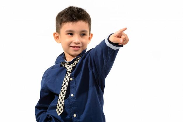 Ładny szczęśliwy chłopiec uśmiecha się i wskazuje palcem