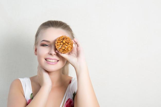 Ładny szczęśliwy dziewczyna obejmujące oko z ciastko, pozowanie na szarym tle. miejsce na tekst