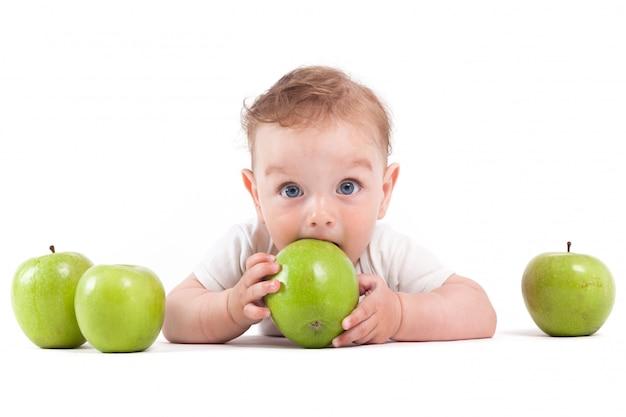 Ładny szczęśliwy mały chłopiec w białej koszuli trzymać zielone jabłko