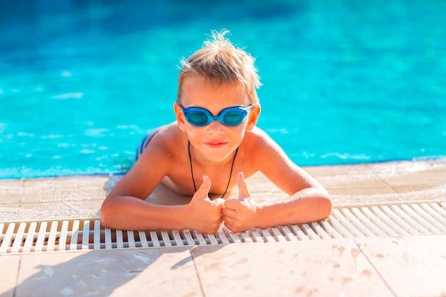 Ładny szczęśliwy mały chłopiec w gogle pływanie i nurkowanie w basenie. koncepcja pływania dla dzieci