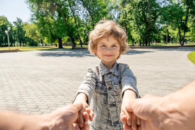 Ładny szczęśliwy mały chłopiec z blond kręconymi włosami patrząc na swojego rodzica, trzymając się za ręce i bawić się w parku z drzewami