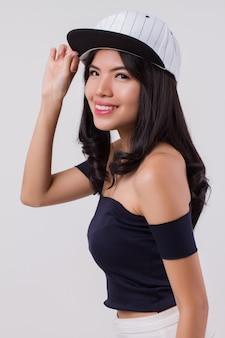 Ładny szczęśliwy uśmiechający się kobieta nosi czapkę. portret pozytywnej optymistycznej kobiety miejskich z nowoczesną modą, studio białe na białym tle z przyjazną twarzą dziewczyny. młoda dorosła piękna dziewczyna azjatycka modelka