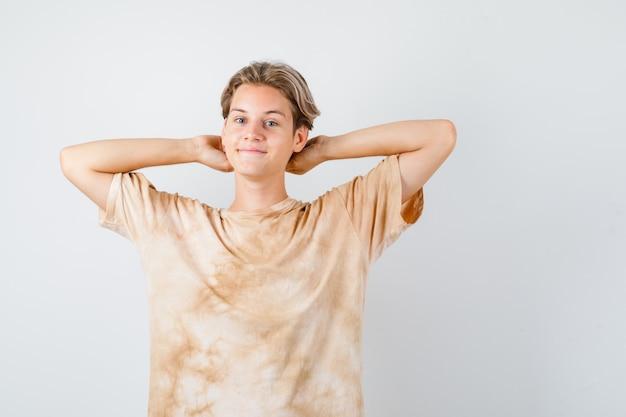 Ładny teen chłopiec trzymając ręce za głowę w t-shirt i patrząc wesoły, widok z przodu.