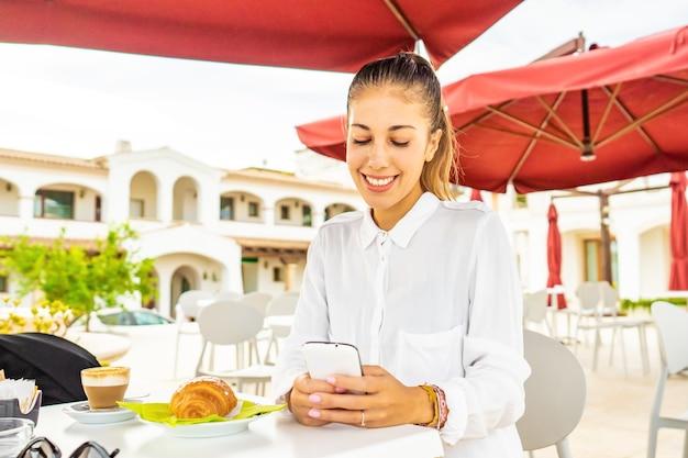 Ładny trzymane włosy dziewczyna w białej koszuli uśmiechający się przy użyciu smartfona przy śniadaniu w hotelowej kawiarni ogród. tysiąclecia hipsterka korzystająca z technologii siedząca przy stole dehors z rogalikiem i cappuccino